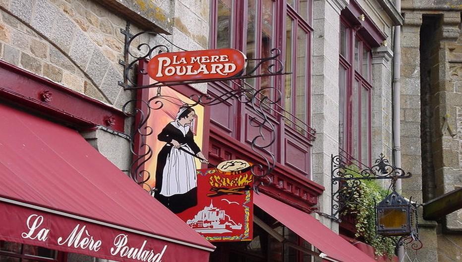 La célèbre enseigne de la Mère Poulard au Mont-Saint-Michel. La Mère Poulard reste ici une ambassadrice privilégiée par la grâce d'une omelette fameuse qui fait le succès de son auberge depuis plus de 150 ans.  © OT Mont-Saint-Michel