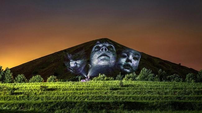 Conçues par l'artiste Clément Lesaffre, des projections de visages des anciens mineurs et des nouvelles générations sur les écrans noirs formés par les terrils. @ Louvre-Lens