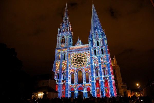 """Portail Royal de la cathédrale jaillissant de la nuit et sur lequel une nouvelle scénographie orchestrée par """"Spectaculaires,les Allumeurs d'images"""" fait revivre, à travers des """"bâtisseurs de lumière"""", toute l'histoire du monument ( Photo M.Anglada)"""