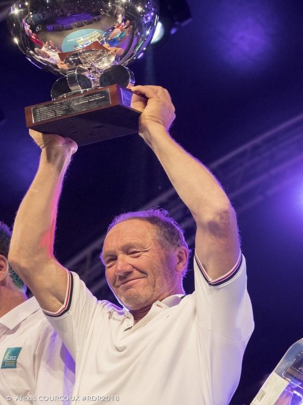 Francis Joyon brandit avec fierté la coupe de sa victoire pour le 40ème anniversaire de la Route du Rhum. Crédit photo DR