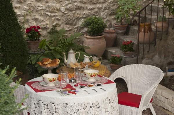 Dans le petit jardin, nappe en dentelle et vaisselle ancienne pour le petit-déjeuner. @ DR