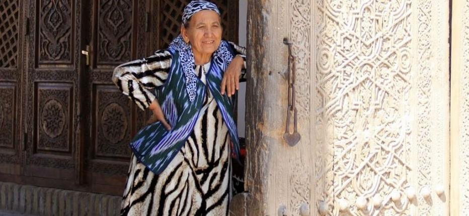 Le sourire accueillant d'une femme Ouzbèque devant le seuil d'une majestueuse porte sculptée.  @ Pixabay